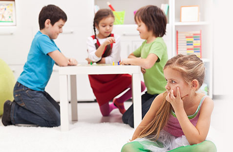child sitting alone at school not joining in